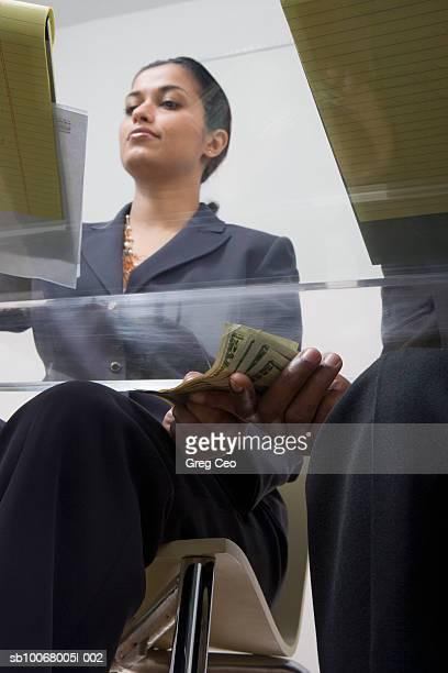 Business woman giving man money under desk