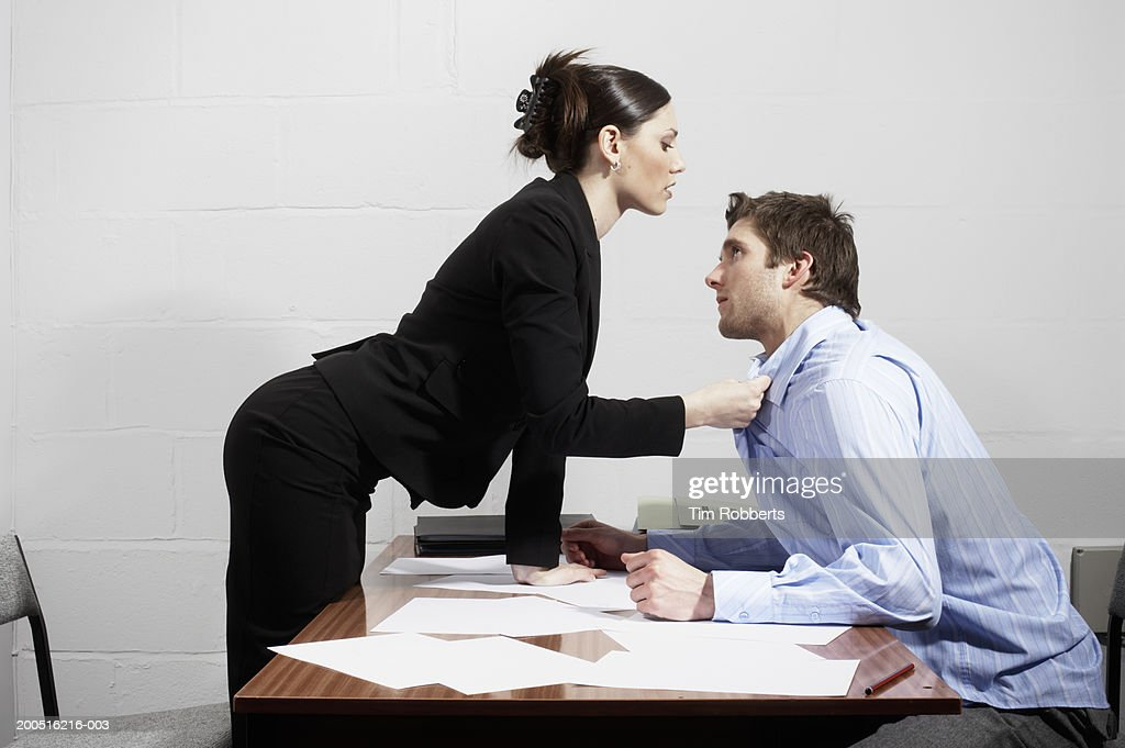Business woman grabbing collar of business man over desk, side view : Stock Photo