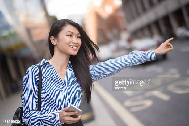 Business woman hailing a taxi