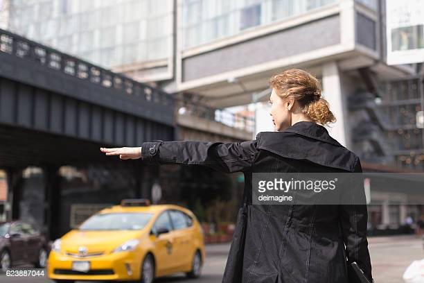 Business Woman hailing taxi in NY city
