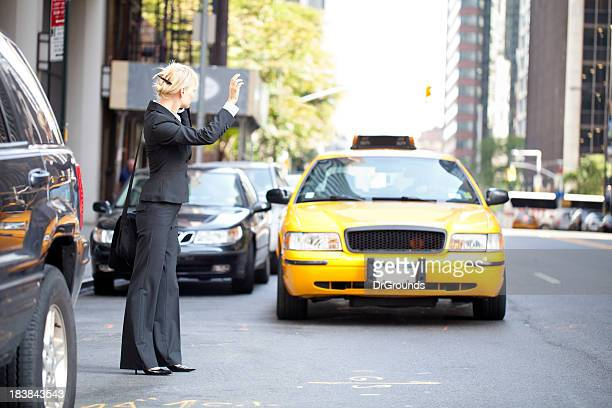 Business woman hailing yellow taxi cab in city