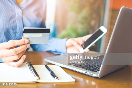 Business woman hand holds a credit card and uses a telephone to shop online. : Stock Photo