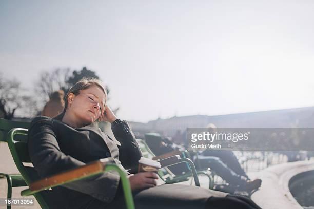 Business woman having a break in park.