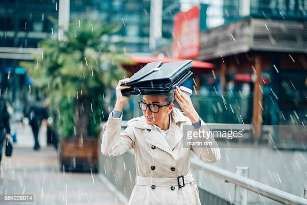 Business woman hiding from the rain