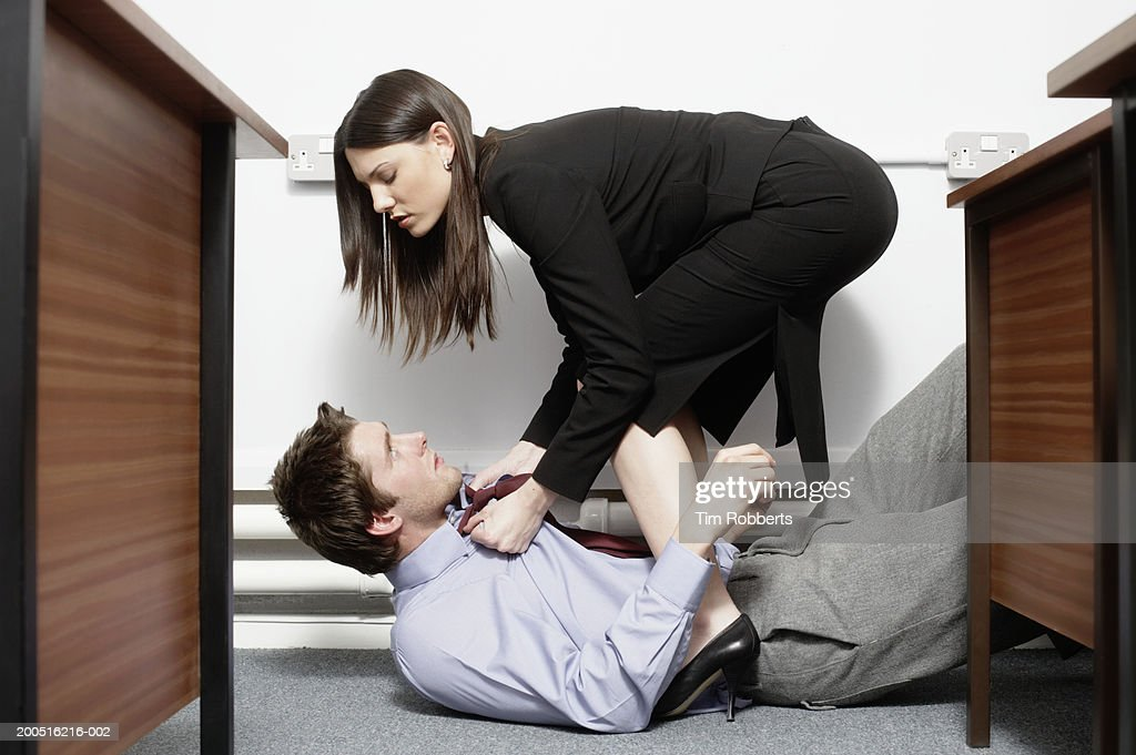 Business woman holding collar of business man on floor in office : Stock Photo