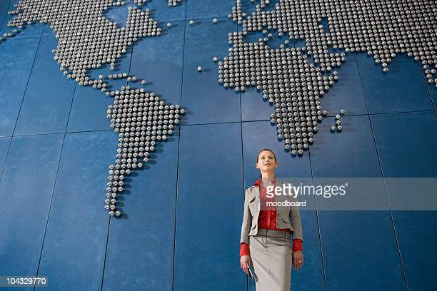 Business woman holding mobile phone, in front of world map in office