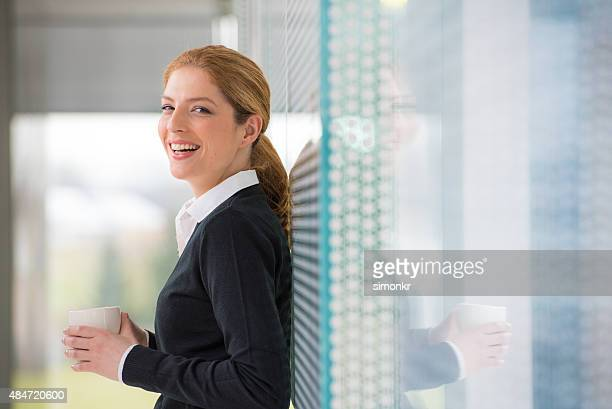 Business woman holding tea cup and laughing