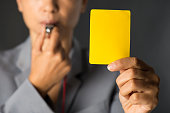 Businesswoman blowing a whistle and showing yellow card.