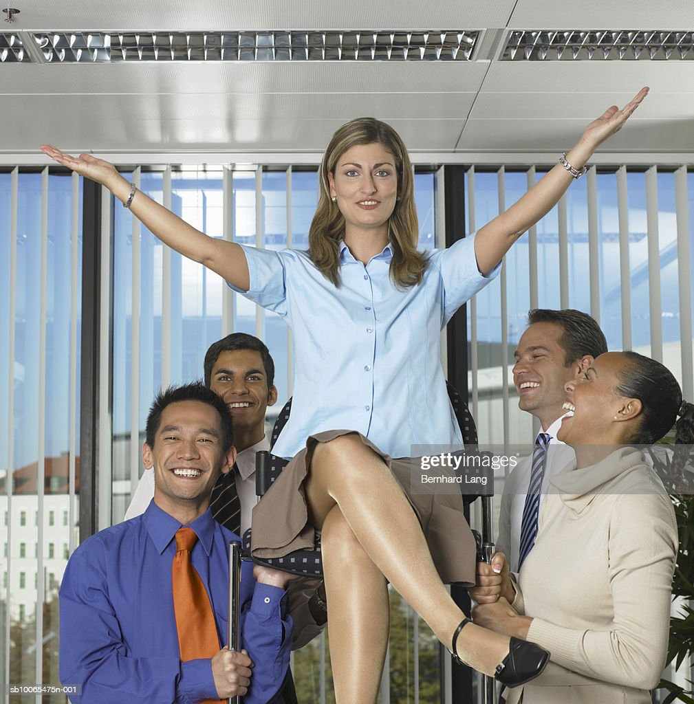 Business woman in chair held aloft by four colleagues : Stock Photo