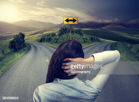 business woman in front of two roads thinking deciding : Stock Photo
