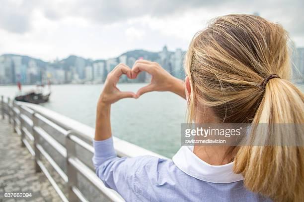 Business woman in Hong Kong makes heart shape finger frame
