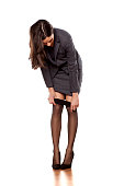 business woman in jacket and skirt puts on her nylon stockings