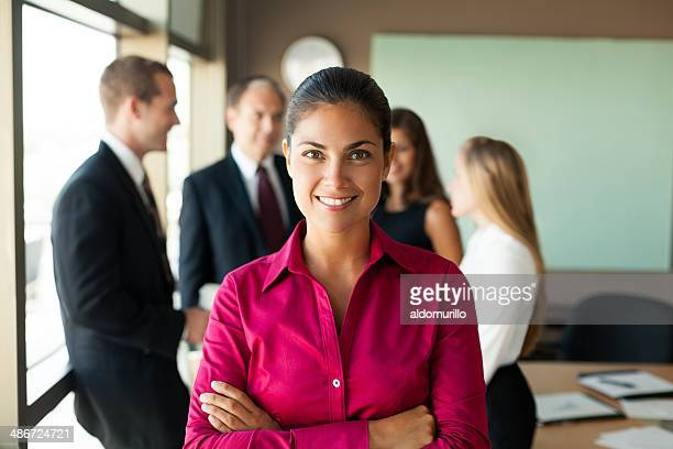 Business woman in meeting with team behind