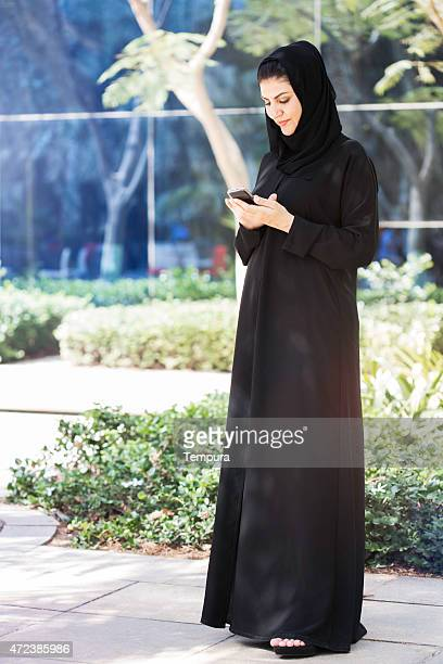 Business woman in suit looking at her phone, Dubai.