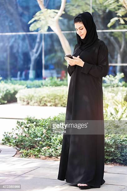 Mujer de negocios en traje mirando su teléfono, Dubai.