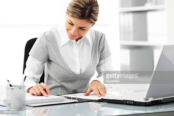 Business woman is reading a note in the office.