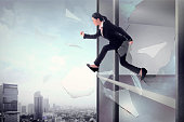 Business woman jump through office window glass. Business freedom concept