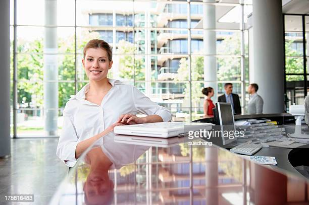Business woman leaning against reception desk
