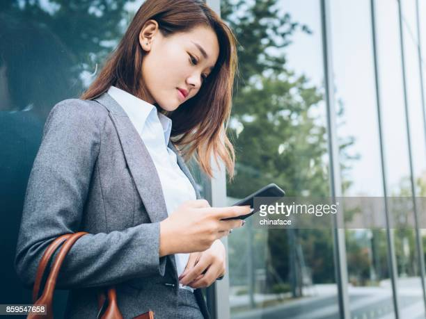 business woman leaning on glass wall using smartphone