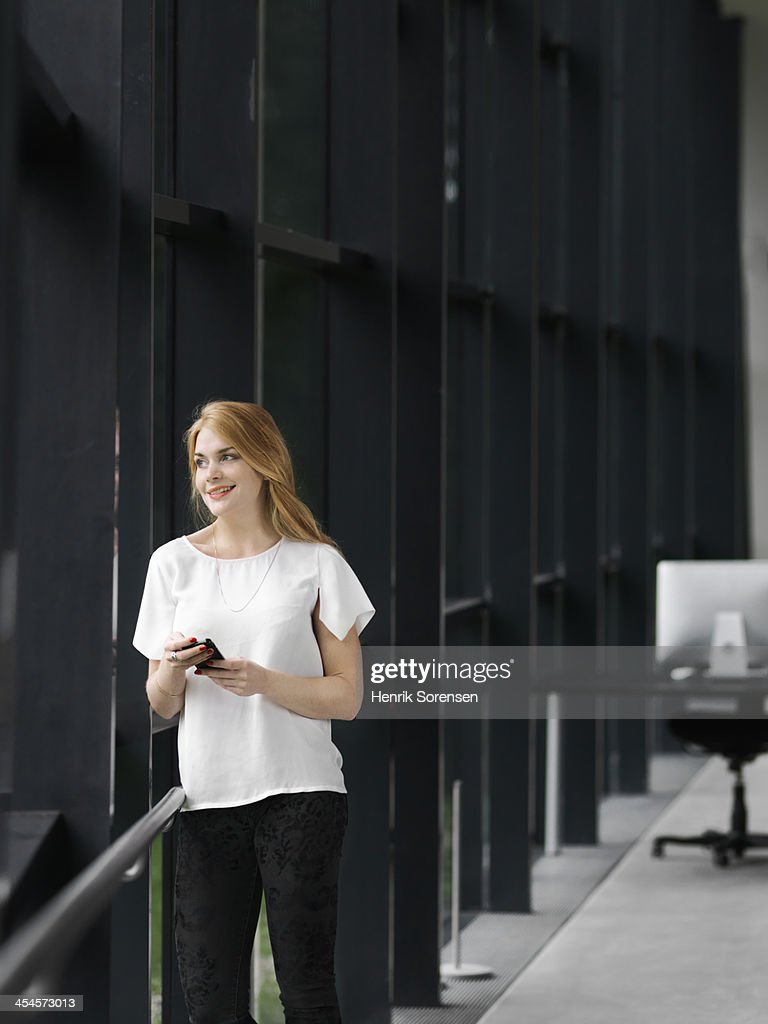 Business woman leaning on railing : Stock Photo