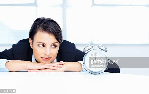 Business woman looking at alarm clock on desk