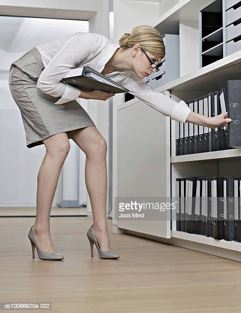 Business woman looking for binder on shelf