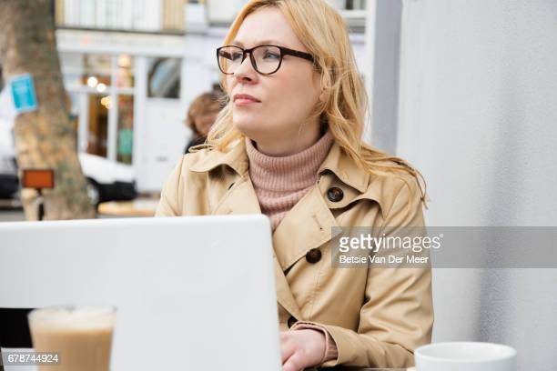 Business woman looks up from laptop, working in outdoor cafe.