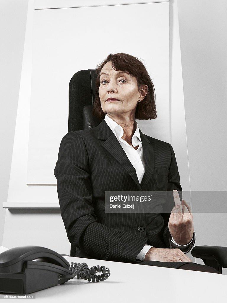 Business woman making hand gesture sitting behind desk, portrait
