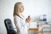 Business and healthy lifestyle concept. Portrait of young office woman standing in yoga pose at workplace. Smiling business lady relaxing with arms folded in Prayer gesture on her break time