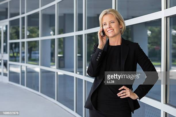Business woman on her cell phone outside of a building