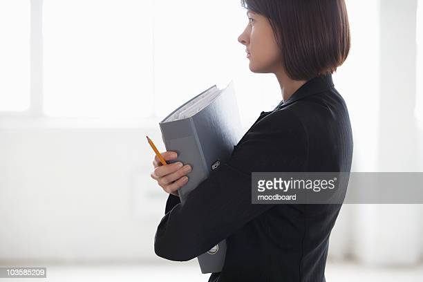 Business woman on holding file in warehouse interior