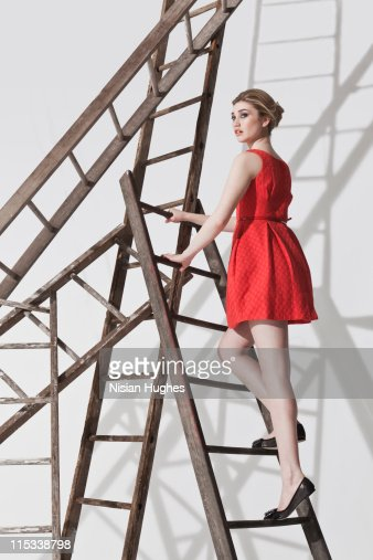 Business woman on ladder construction