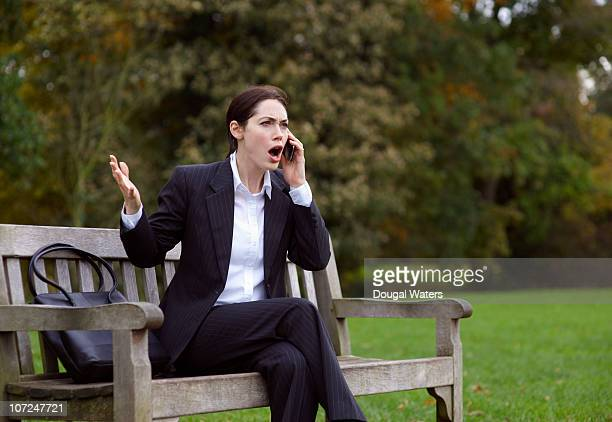 Business woman on park bench using mobile phone.