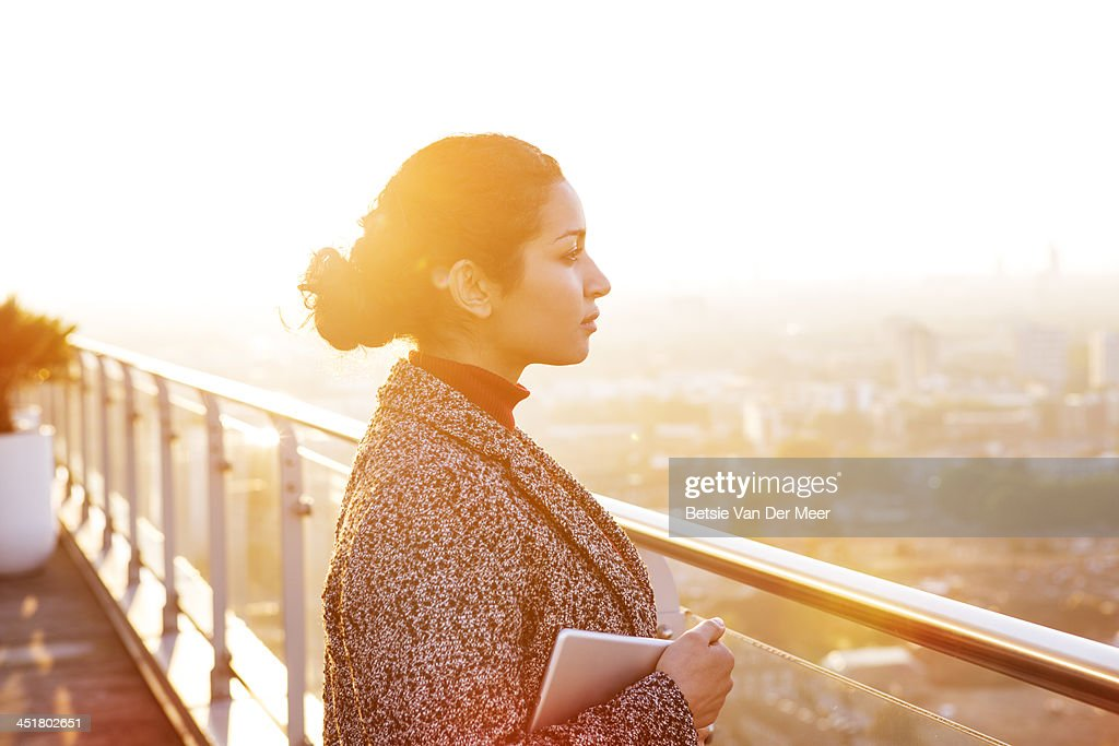 Business woman overlooks city, wireless device. : Stock Photo