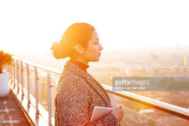 Business woman overlooks city, wireless device.