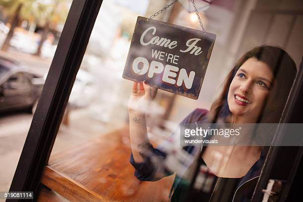 Business woman owner Turning Opening Sign on Door Coffee Shop