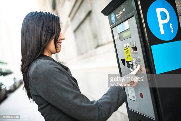 business woman paying th parking at the machine