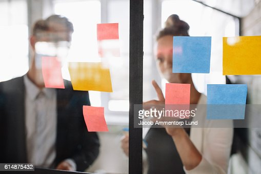 Business woman pointing at sticky note to male colleague : Stock Photo