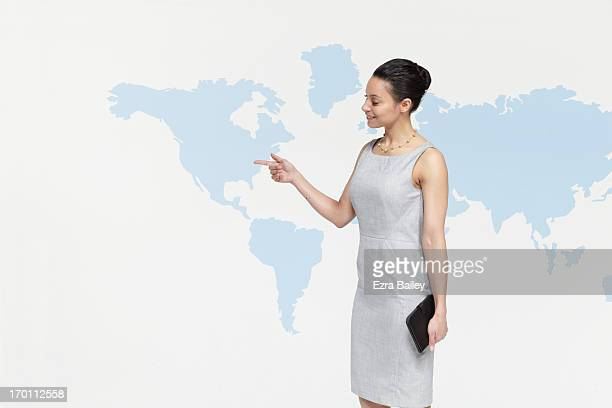 Business woman pointing to world map.