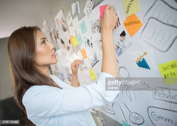 Business woman posting on a wall chart