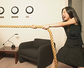 Business woman pulling a rope in the office