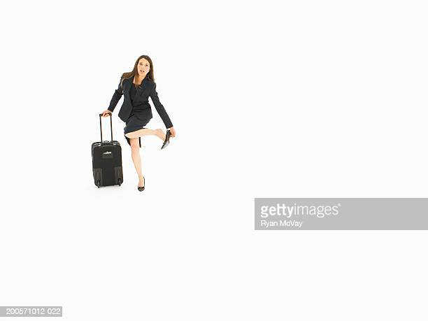 Business woman pulling suitcase and adjusting shoe