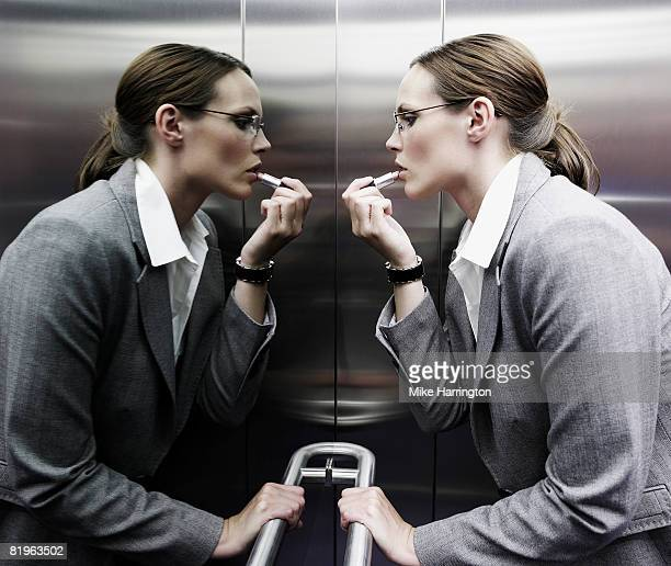 Business woman putting lip stick on in the lift mirror