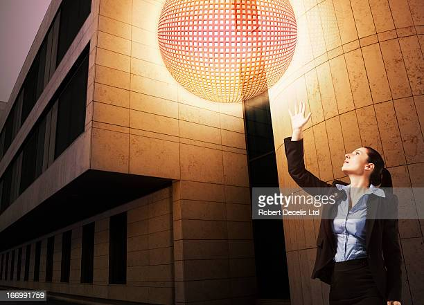 Business woman reaching out to sphere of energy