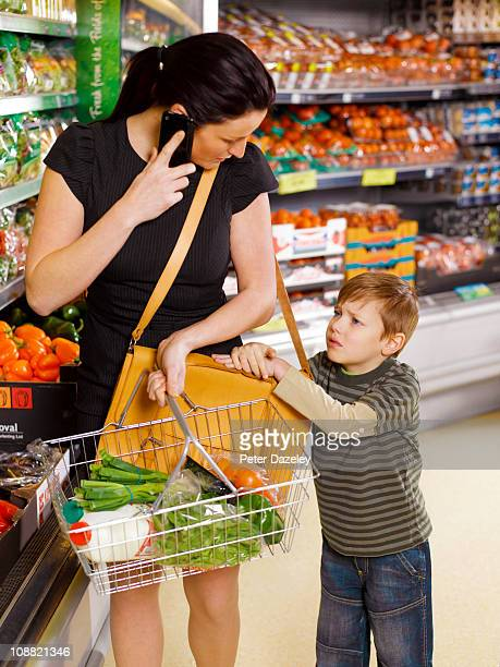 Business woman shopping with unhappy son
