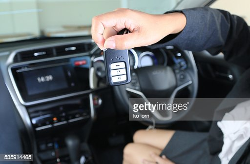 Business woman show remote key in modern vehicle car. : Stock Photo