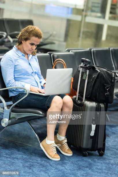 Business-Frau sitzt am Flughafen-terminal