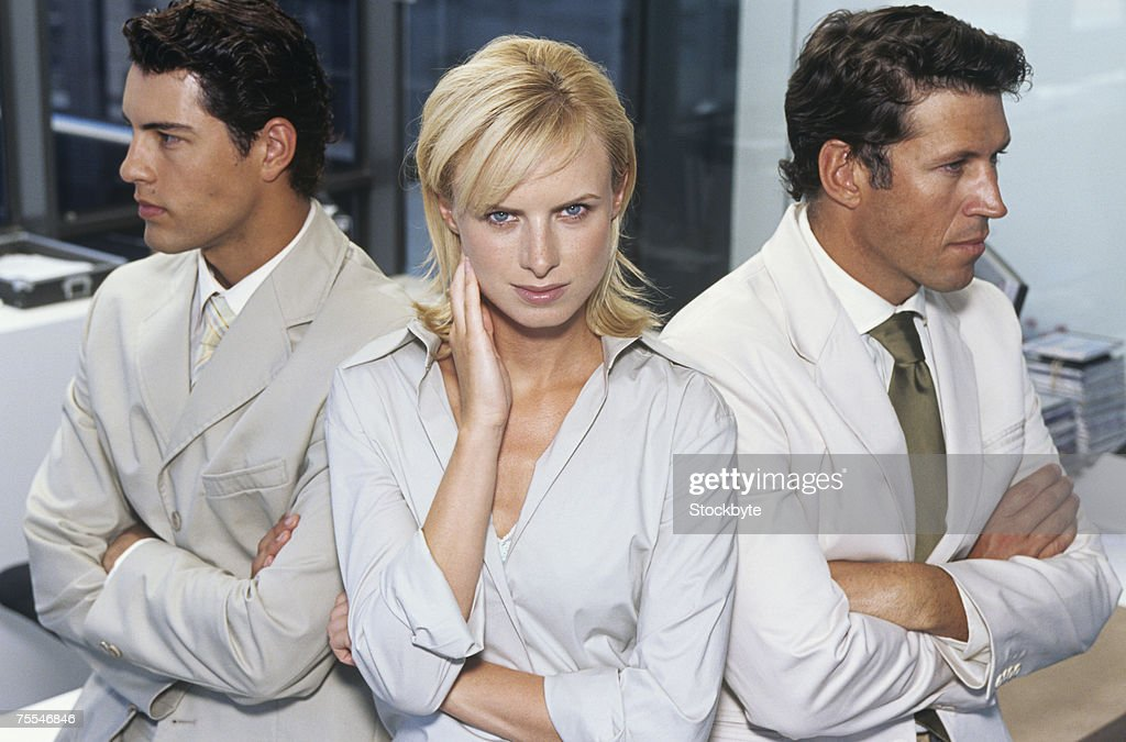 Business woman sitting between two business men in office,elevated view
