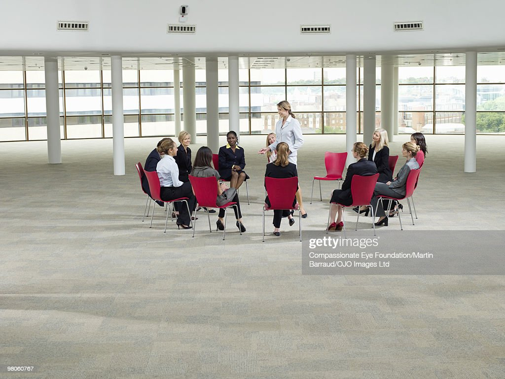 business woman sitting in a circle on red chairs : Stock Photo