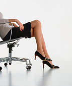 Business woman dressed with elegance sitting in an armchair, free space for text